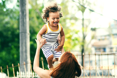 Caucasian female playfully tossing toddler in air. The two are smiling at each other and look unaware of camera.