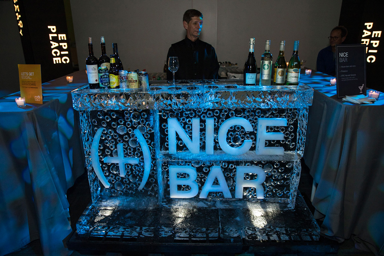A bar made of a block of ice with a bartender behind it.