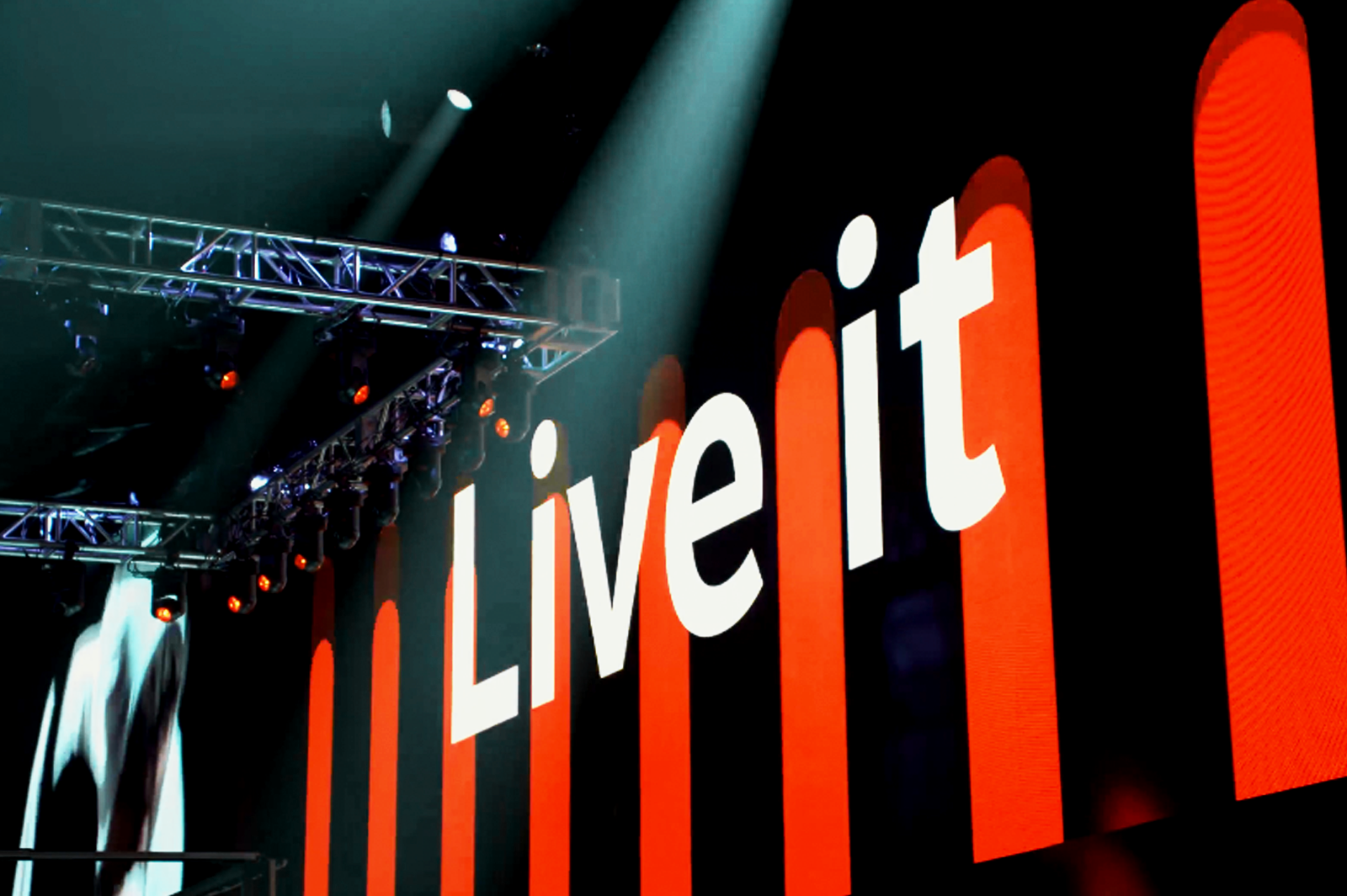 Angled photo of lighting design and LED screen at conference with red and black design and the words Live it on screen.