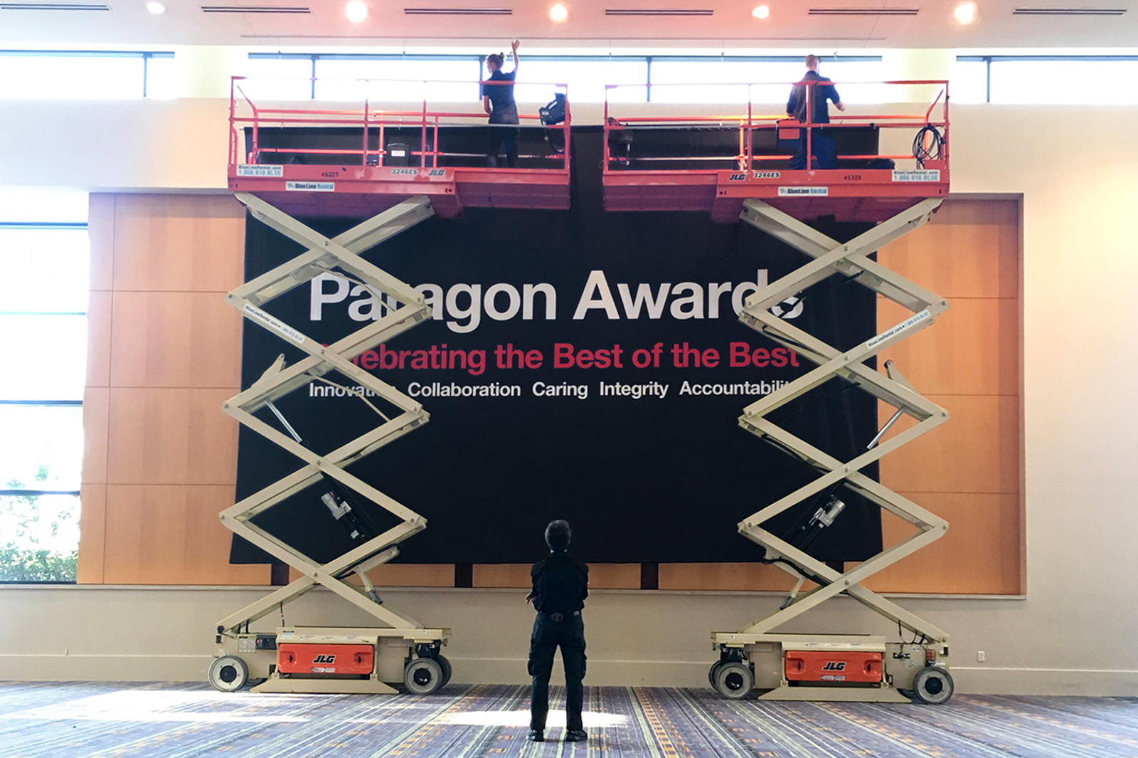 CVS Paragon Awards banner being raised by add ventures crews with cherry pickers.